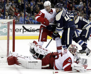Photo - Columbus Blue Jackets' Artem Anisimov (42) scores against Detroit Red Wings' Kent Huskins (3) and goalie Jimmy Howard (35) in the second period of an NHL hockey game in Columbus, Ohio, Saturday, Feb. 2, 2013. (AP Photo/Paul Vernon)