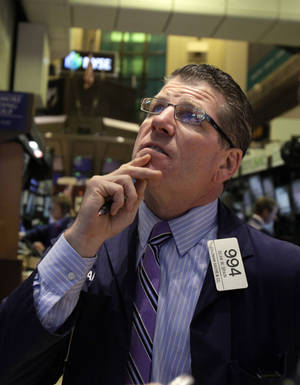 Photo -   FILE -- A July 26, 2012 file photo shows trader Sean Spain working on the floor of the New York Stock Exchange. A stock market rally lost steam Wednesday Aug. 8, 2012 after mixed earnings from U.S. companies added to fears about Europe's economic slowdown. (AP Photo/Richard Drew/file)