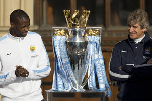 Photo - Manchester City's Yaya Toure, left, and manager Manuel Pellegrini stand by the trophy as the team celebrate in the city centre the day after they won the English Premier League title, Manchester, England, Monday May 12, 2014. (AP Photo/Jon Super)