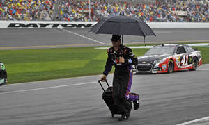 Photo - A crew member runs down pit road during a rain delay in the NASCAR Daytona 500 Sprint Cup series auto race at Daytona International Speedway in Daytona Beach, Fla., Sunday, Feb. 23, 2014. (AP Photo/Terry Renna)