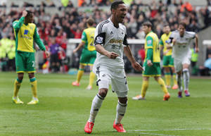 Photo - Swansea City's Jonathan de Guzman celebrates scoring the opening goal against Norwich City during their English Premier League soccer match at the Liberty Stadium, Swansea, Wales, Saturday, March 29, 2014. (AP Photo/Nick Potts, PA Wire)    UNITED KINGDOM OUT   -   NO SALES   -   NO ARCHIVES