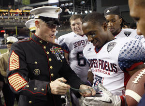 Photo - Marine Sgt. Maj. Michael Barrett, left, awards the Semper Fidelis All-American Bowl high school football game MVP trophy to West All American Jaydon Mickens at Chase Field, Tuesday, Jan. 3, 2012, in Phoenix. West defeated East 17-14. (AP Photo/Matt York) ORG XMIT: PNC110