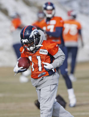 Photo - Denver Broncos wide receiver Trindon Holliday (11) pulls in a pass during practice for the football team's NFL playoff game against the San Diego Chargers at the Broncos training facility in Englewood, Colo., on Friday, Jan. 10, 2014. Special teams has turned into the Broncos' bugaboo with at least one major mistake in each of the last six games, and Trindon Holliday has had six muffs in the last two months. He also entered last year's playoffs in a prolonged slump and promptly became the first player in league history to return both a punt and a kickoff for touchdowns in the postseason.(AP Photo/Ed Andrieski)