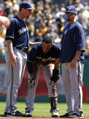 Photo - Milwaukee Brewers' Carlos Gomez, center, catches his breath after participating in a brawl with the Pittsburgh Pirates during the third inning of a baseball game in Pittsburgh, Sunday, April 20, 2014. Gomez and Pirates' Travis Snider were ejected from the game. (AP Photo/Gene J. Puskar)