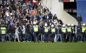"Photo - Swedish police try to handle supporters of Stockholm soccer club Djurgarden that stormed the pitch during the Swedish league match between Helsingborgs IF and Djurgarden IF held at Olympia in Helsingborg, Sweden, Sunday March 30 2014. The match was called off during the first half Sunday after a Djurgarden supporter died following clashes between fans in the southern city of Helsingborg. Police said the man was found ""seriously injured"" in central Helsingborg around 2:30 p.m. Sunday and was taken to a hospital, where he later died. Local media said the 44-year-old Djurgarden supporter had been hit in the head by an object after rival fans started fighting before the game. (AP Photo/Bjorn Lindgren, TT News Agency)     SWEDEN OUT"