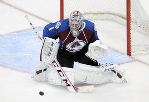 Photo - Colorado Avalanche goalie Semyon Varlamov, of Russia, makes a save in the first period of an NHL hockey game against the San Jose Sharks on Saturday, Jan. 4, 2014, in Denver.  (AP Photo/Chris Schneider)