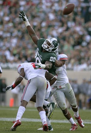 Photo -   Michigan State's Dion Sims (80) is unable to hang on to a pass as he is hit by Ohio State's Rod Smith, left, and Etienne Sabino during the fourth quarter of an NCAA college football game, Saturday, Sept. 29, 2012, in East Lansing, Mich. Ohio State won 17-16. (AP Photo/Al Goldis)
