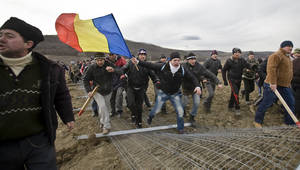 Photo - Anti-shale gas exploration protesters bring down a fence in Pungesti, north eastern Romania, Saturday, Dec. 7, 2013. Hundreds of villagers destroyed the fences around a plot of land owned by US energy company Chevron, during protests meant to stop shale gas exploration in the area. (AP Photo/Mircea Restea)