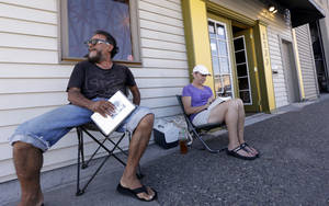 Photo - George Vargas, left, takes a seat next to first-in-line customer Deb Greene in front of the recreational marijuana store Cannabis City Monday, July 7, 2014, in Seattle. The store will be the first and only store initially in Seattle to legally sell recreational pot when sales begin Tuesday. (AP Photo/Elaine Thompson)