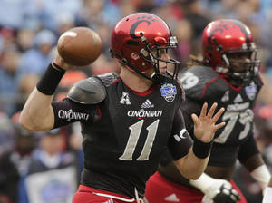 Photo - Cincinnati quarterback Brendon Kay (11) looks to pass against North Carolina during the first half of the Belk Bowl NCAA college football game , Saturday, Dec. 28, 2013, in Charlotte, N.C. (AP Photo/Nell Redmond)