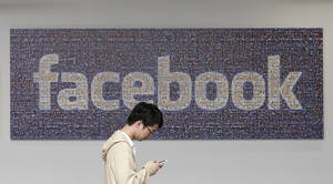Photo - In this June 11, 2014 photo, a man walks past a Facebook sign in an office on the Facebook campus in Menlo Park, Calif. British data protection authorities said Wednesday, July 2, that it is investigating revelations that Facebook conducted a psychological experiment on its users. (AP Photo/Jeff Chiu)