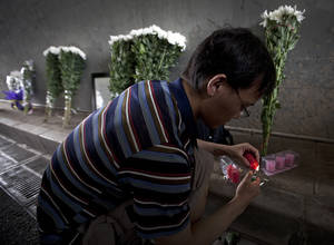 Photo -   A man lights candles near the flowers placed under a railway bridge, where a motorist drowned a week ago in Beijing, China Saturday, July 28, 2012. A small group of people laid down white chrysanthemums or lit candles Saturday to pay tribute to those who died in the storm that ravaged Beijing one week ago, killing at least 77. (AP Photo/Andy Wong)