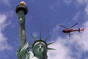 Photo - One of three helicopters showered 1-million rose petals on the Statue of Liberty during a ceremony commemorating the 70th anniversary of the D-Day invasion, on Liberty Island in New York Harbor, Friday, June 6, 2014. (AP Photo/Richard Drew)