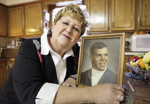 photo - Janet Miller shown in December 2010 with a photo of her husband, George, who was killed during blizzard conditions on Christmas Eve in 2009. Photo by David McDaniel, The Oklahoman Archives