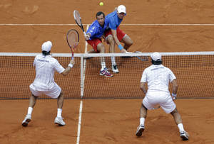Photo -   Czech Republic's Tomas Berdych, right, and Radek Stepanek, left, returns the ball to Argentina's Eduardo Schwank, right below, and Carlos Berlocq during their doubles match of the Davis Cup tennis semifinals in Buenos Aires, Argentina, Saturday, Sept. 15, 2012. (AP Photo/Natacha Pisarenko)