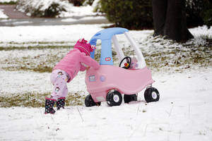 Photo - Molly Cleland, two and a half,  pushes her car through the snow in Jackson, Miss., Thursday,  Jan. 17, 2013.  A winter storm system left 2 to 4 inches of snow in parts of central Mississippi before heading east toward Alabama, the National Weather Service said. (AP Photo/Rogelio V. Solis)