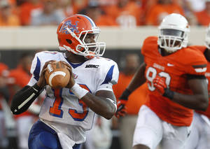 Photo -   Savannah State quarterback Antonio Bostick (13) scrambles under pressure from Oklahoma State defensive tackle Davidell Collins (98) in the second quarter of an NCAA college football game in Stillwater, Okla., Saturday, Sept. 1, 2012. (AP Photo/Sue Ogrocki)