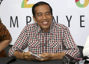 "Photo - Indonesian presidential candidate Joko Widodo, popularly known as ""Jokowi"" smiles during a press conference in Jakarta, Indonesia, Thursday, July 10, 2014. Jakarta Governor Joko ""Jokowi"" Widodo and former army general Prabowo Subianto are both claiming victory in Indonesia's presidential election based on unofficial ""quick counts,"" raising the specter of prolonged political instability in Southeast Asia's largest economy. (AP Photo/Tatan Syuflana)"