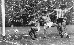 Photo - FILE - In this Sunday, June 25, 1978 file photo, Mario Kempes of Argentina, right, celebrates, after scoring Argentina's second goal against the Netherlands, during their World Cup final soccer match, at the River Plate Stadium, in Buenos Aires, Argentina. At left is Dutch player Ruud Krol, and Poortvliet at centre.  On this day: Argentina wins its first World Cup in front of a confetti-laden crowd. (AP Photo/File)
