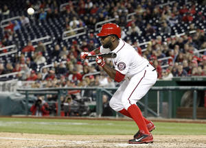 Photo - Washington Nationals' Denard Span bunts the ball, and reached second on a throwing error, during the eighth inning of a baseball game against the Miami Marlins at Nationals Park Wednesday, April 9, 2014, in Washington. The Nationals won 10-7. (AP Photo/Alex Brandon)