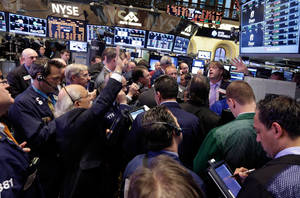 Photo - Traders gather at a post on the floor of the New York Stock Exchange at the close of trading on Thursday. Investors appear to be getting more comfortable owning riskier stocks, as technology companies have been among the best gainers lately, while safer stocks like utitlities and consumer staples firms have been flat. <strong>Richard Drew - AP</strong>