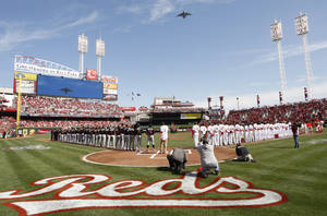 Photo -   The Cincinnati Reds and the Miami Marlins stand on the field during the National Anthem prior to an Opening Day baseball game, Thursday, April 5, 2012, in Cincinnati. (AP Photo/David Kohl)