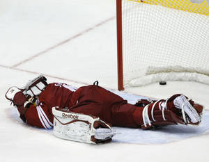 Photo - Phoenix Coyotes goalie Mike Smith (41) lies on the ice after getting hit in the second period during an NHL hockey game against the Detroit Red Wings on Saturday, Oct. 19, 2013, in Glendale, Ariz. The goal was disallowed after a review. (AP Photo/Rick Scuteri)