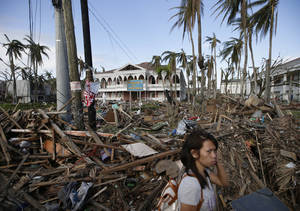 Photo - A typhoon survivor walks past the debris-littered Sto. Nino Shrine and Heritage Museum which used to house former Philippine First Lady Imelda Marcos' collection of art pieces from Philippine national artists Sunday Nov. 17, 2013 at  Tacloban city, Leyte province in central Philippines. Typhoon Haiyan, one of the most powerful typhoons ever recorded, slammed into central Philippine provinces Nov.8, leaving a wide swath of destruction and thousands of people dead.(AP Photo/Bullit Marquez)