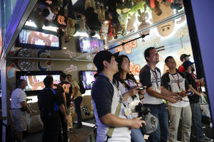 "Photo - Show attendees play  the ""LittleBigPlanet 3"" video game at the Sony booth at the Electronic Entertainment Expo on Tuesday, June 10, 2014, in Los Angeles. (AP Photo/Jae C. Hong)"