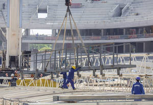 Photo - In this Dec. 4, 2013 photo released by Portal da Copa, personnel continue construction on the Arena da Baixada stadium in Curitiba, Brazil. Brazilian authorities said on Wednesday, Jan. 29, 2014 that the pace of construction has improved at this delayed World Cup stadium and are optimistic the city will still be able to host games. FIFA said local officials have until Feb. 18, 2014 to show the city will be able to finish the stadium in time and football's governing body will make its own evaluation to decide whether to keep games in Curitiba. (AP Photo/Alexandre Carnieri, Portal da Copa)