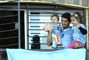Photo - Uruguay's soccer player Luis Suarez, center, with his children Benjamin, left, and Delfina, waves to fans from his home, before the start of his team's World Cup round 16 match with Colombia, on the outskirts of Montevideo, Uruguay, Saturday, June 28, 2014. FIFA banned Suarez from all football activities for four months for biting an opponent at the World Cup, a punishment that rules him out of the rest of the tournament. (AP Photo/Matilde Campodonico)