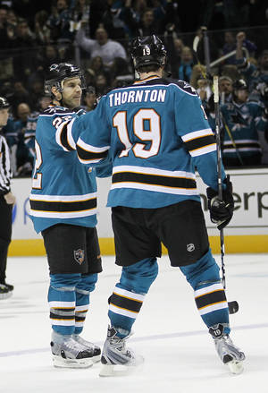Photo - San Jose Sharks defenseman Dan Boyle (22) is congratulated by Joe Thornton (19) after scoring a goal against the Nashville Predators during the first period of an NHL hockey game in San Jose, Calif., Saturday, March 2, 2013. (AP Photo/Tony Avelar)