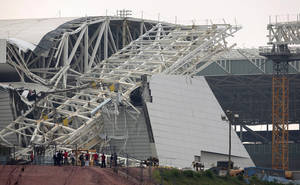 Photo - FILE - In this Nov. 27, 2013 file photo, a buckled metal structure sits on a part of the Itaquerao Stadium in Sao Paulo, Brazil. A news report cites Sao Paulo state Labor Ministry official Luis Antonio Medeiros as saying the man who operated the crane that collapsed at the city's World Cup stadium had worked 18 days in a row. Two construction workers were killed in the accident, which remains under investigation. The stadium is slated to host the 2014 World Cup opener. (AP Photo/Andre Penner, File)
