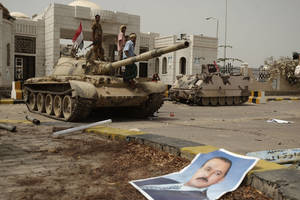 Photo -   A poster of Yemen's former President Ali Abdullah Saleh lies on the ground as army soldiers and tribesmen loyal to the army gather on a tank in front of the local authority compound in the city of Zinjibar, Yemen after they retook the city from al-Qaida militants, Thursday, June 14, 2012. Airstrikes and clashes intensified in southern Yemen on Wednesday as army troops followed major victories with more pressure on al-Qaida militants holding small towns, according to tribal and military officials. The attacks came a day after Yemeni forces regained control of two major al-Qaida strongholds, Jaar and Zinjibar, which were in the hands of the militants for more than a year. (AP Photo/Hani Mohammed)