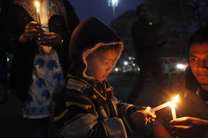 photo - A young boy participates in a candlelight vigil protesting against a leader of the ruling Congress party on accusations he raped a woman in a village in the early hours of the morning, in Gauhati, India, Friday, Jan. 4, 2013. Footage on Indian television showed the extraordinary scene of local women surrounding Bikram Singh Brahma, ripping off his shirt and repeatedly slapping him across the face. A Dec. 16 gang rape on a woman, who later died of her injuries, has caused outrage across India, sparking protests and demands for tough new rape laws, better police protection for women and a sustained campaign to change society's views about women. (AP Photo/Anupam Nath)