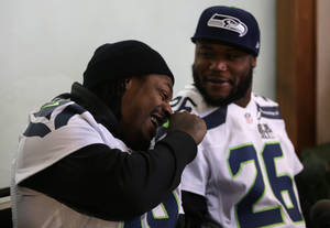 Photo - Seattle Seahawks running back Marshawn Lynch, left, laughs with teammate Michael Robinson as they participate in a media availability Thursday, Jan. 30, 2014, in Jersey City, N.J. The Seahawks and the Denver Broncos are scheduled to play in the Super Bowl XLVIII football game Sunday, Feb. 2, 2014. (AP Photo)