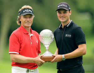 photo - German golfer Bernhard Langer, left, with fellow country man Martin Kaymer, right, holds a trophy after winning the final round of the Nedbank Champions Challenge seniors event at the Gary Player Country Club in Sun City, South Africa, Saturday, Dec. 1, 2012. Kaymer, holds a one-stroke lead on Saturday, heading into the final round of the Nedbank Golf Challenge. (AP Photo/Themba Hadebe)
