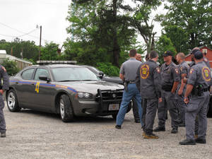 Photo -   Members of the Mississippi Highway Patrol gather at a staging area during the search for a missing Tennessee family, Monday, May 7 2012 in Guntown, Miss. State troopers stopped vehicles at roadblocks Monday and officers searched the yard of a home in northern Mississippi, seeking to unravel the mysterious disappearance of a Tennessee mother and her three daughters and find the family friend accused of abducting them. (AP Photo/Adrian Sainz)