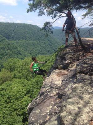 Photo - This Friday June 20, 2014 photo provided by Andrea Ness shows her repelling Bridge Buttress in the New River Gorge near Fayetteville, W. Va.  Trips sold on the state's showcase New River are down so far this year, and at least one whitewater industry official is blaming a January chemical spill in Charleston for putting at least a slight damper on tourism in the region.  (AP Photo/Duston Twichell)