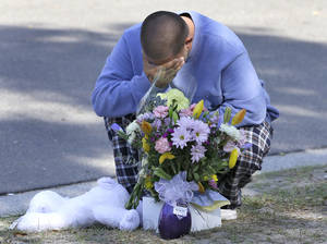 photo - Jeremy Bush places flowers and a stuffed animal at a makeshift memorial in front of a home where a sinkhole opened up underneath a bedroom late Thursday evening and swallowed his brother Jeffrey in Seffner, Fla. on Saturday, March 2, 2013.   Jeffrey Bush, 37, was in his bedroom Thursday night when the earth opened and took him and everything else in his room. Five other people were in the house but managed to escape unharmed. Bush's brother jumped into the hole to try to help, but he had to be rescued himself by a sheriff's deputy.  (AP Photo/Chris O'Meara)
