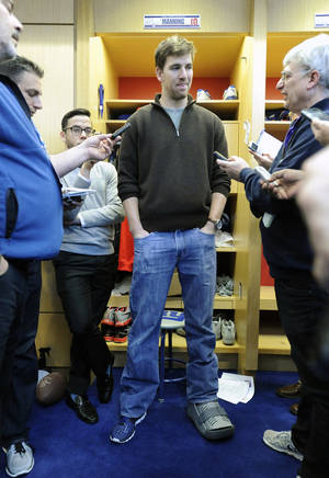 Photo - FILE - In this Dec. 30, 2013 file photo, New York Giants quarterback Eli Manning speaks to the media with a walking boot on his left foot after injuring his ankle in the last game of the season against the Washington Redskins, in East Rutherford, N.J. Eli Manning is going to start the offseason training program with a surgically repaired left ankle. The Giants announced that Manning will have arthroscopic surgery on Thursday, April 10, 2014,  to relieve some lingering discomfort in the ankle he sprained in the regular season finale. (AP Photo/Bill Kostroun, File)