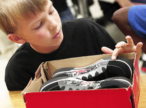 Photo - Luke Hahn checks out the soles of his new shoes. More than 60 fourth-graders at Traub Elementary School in Midwest City received new shoes. Photos by Jim Beckel, The Oklahoman