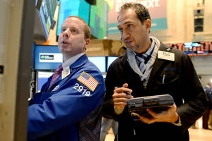 Photo -   FILE -In this Thursday, Nov. 8, 2012, file photo, Robert Nelson II of Barclays, left, and Fady Tanios of Raven Securities work on the floor of the New York Stock Exchange, in New York. (AP Photo/Henny Ray Abrams)