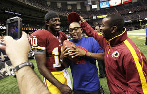 Photo -   Washington Redskins quarterback Robert Griffin III (10) poses for a photo with filmmaker Spike Lee, center, after an NFL football game against the New Orleans Saints in New Orleans, Sunday, Sept. 9, 2012. The Redskins won 40-32. (AP Photo/Matthew Hinton)