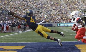 Photo - California wide receiver Kenny Lawler (4) catches a 3-yard touchdown pass from quarterback Jared Goff past Arizona cornerback Jonathan McKnight, right, during the third quarter of an NCAA college football game in Berkeley, Calif., Saturday, Nov. 2, 2013. (AP Photo/Jeff Chiu)