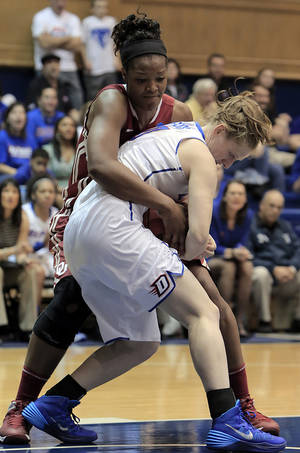 Photo - Oklahoma's Kaylon Williams, background, ties-up DePaul's Kelsey Reynolds during the first half of their first-round game in the NCAA basketball tournament in Durham, N.C., Saturday, March 22, 2014. (AP Photo/Ted Richardson)