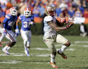 Photo - Florida State wide receiver Kelvin Benjamin tries but cannot hang on to a pass in front of Florida defenders William Few (48) and Cody Riggs (31) during the second half of an NCAA college football game in Gainesville, Fla., Saturday, Nov. 30, 2013. Florida State defeated Florida 37-7.(AP Photo/John Raoux)