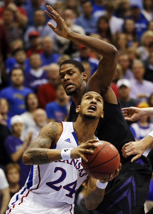 Photo - Kansas guard Travis Releford (24) drives past Kansas State forward Jordan Henriquez, back, during the first half of an NCAA college basketball game in Lawrence, Kan., Monday, Feb. 11, 2013. (AP Photo/Orlin Wagner)