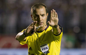 Photo - FILE - In this Tuesday Sept. 10, 2013 file photo, referee Mark Geiger signals a call at a 2014 World Cup qualifier soccer match between Honduras and Panama in Tegucigalpa, Honduras. Mark Geiger aims to become the first American referee to advance from the group stage in the World Cup in Brazil. (AP Photo/Moises Castillo, File)