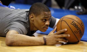 Photo - Oklahoma City's Russell Westbrook (0) stretches on the court before an NBA basketball game between the Oklahoma City Thunder and the Sacramento Kings at Chesapeake Energy Arena in Oklahoma City, Monday, April 15, 2013. Photo by Nate Billings, The Oklahoman